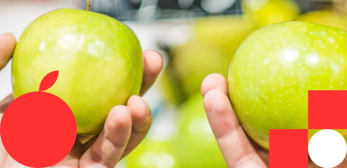 A metaphor for the mobile app development market — a person holding two seemingly identical apples as if trying to choose between an average app and one with a 5-star rating.